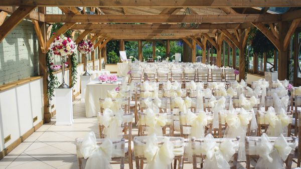 The Orangery is decorated with white ribbons and pink flowers ready for a wedding ceremony