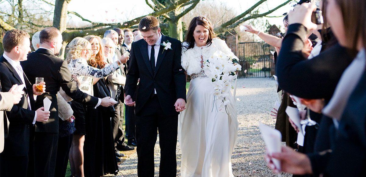 Wedding guests throw confetti during winter wedding at Gaynes Park