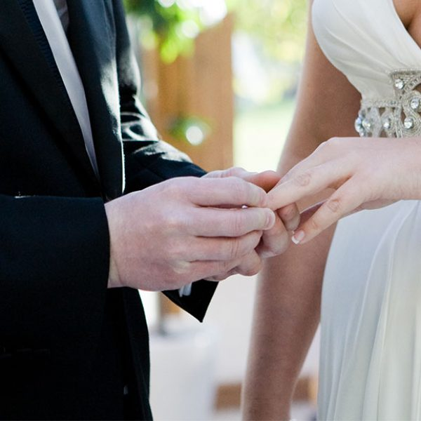 Exchanging rings during their barn wedding ceremony