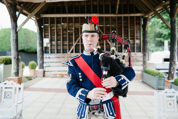 A piper plays the bagpipes for wedding music in the Gather Barn wedding barn