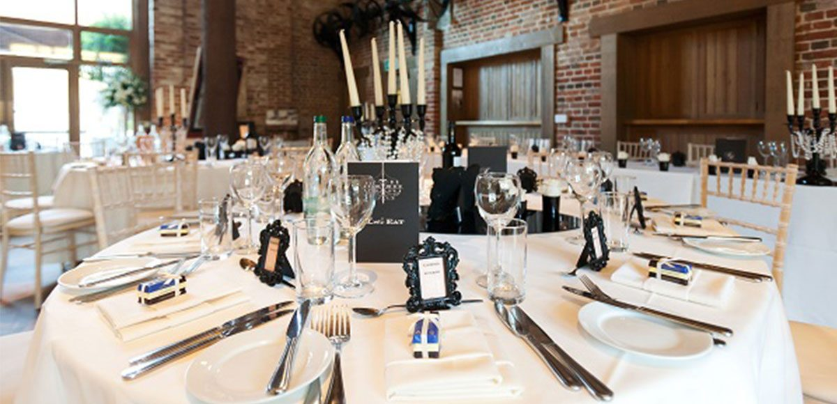 Black and white table decorations set out in the Mill Barn – barn weddings Essex