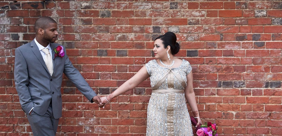Bride and groom pose for photos in the grounds of their Essex wedding venue