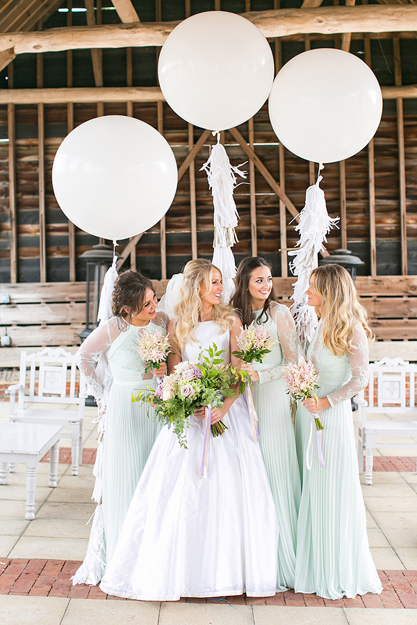 A bride chats with her bridesmaids in the beautiful barn wedding venue - wedding balloon displays