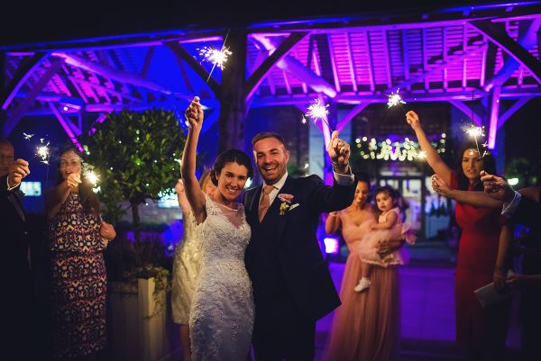 A happy couple light sparklers by the Gather Barn with their wedding guests during their wedding reception