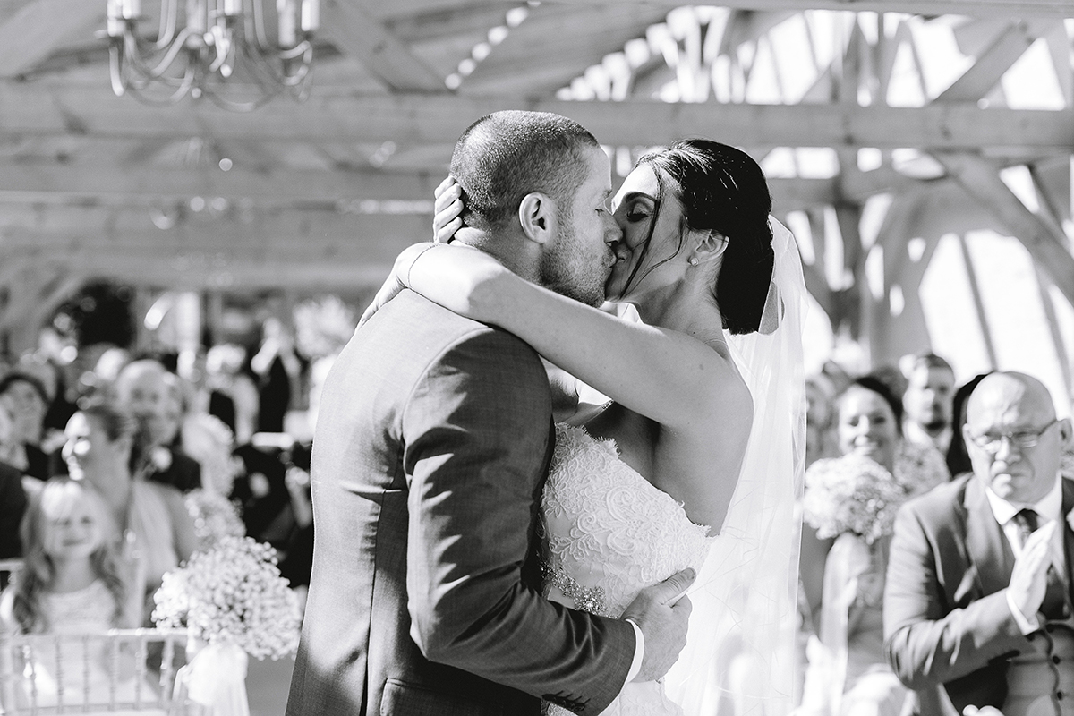 A happy couple seal their wedding ceremony with a kiss - wedding barns Essex