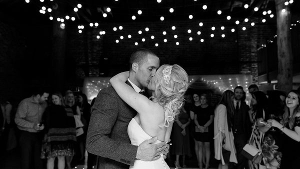 A happy couple steal a kiss on the dancefloor during their evening wedding reception in the Mill Barn