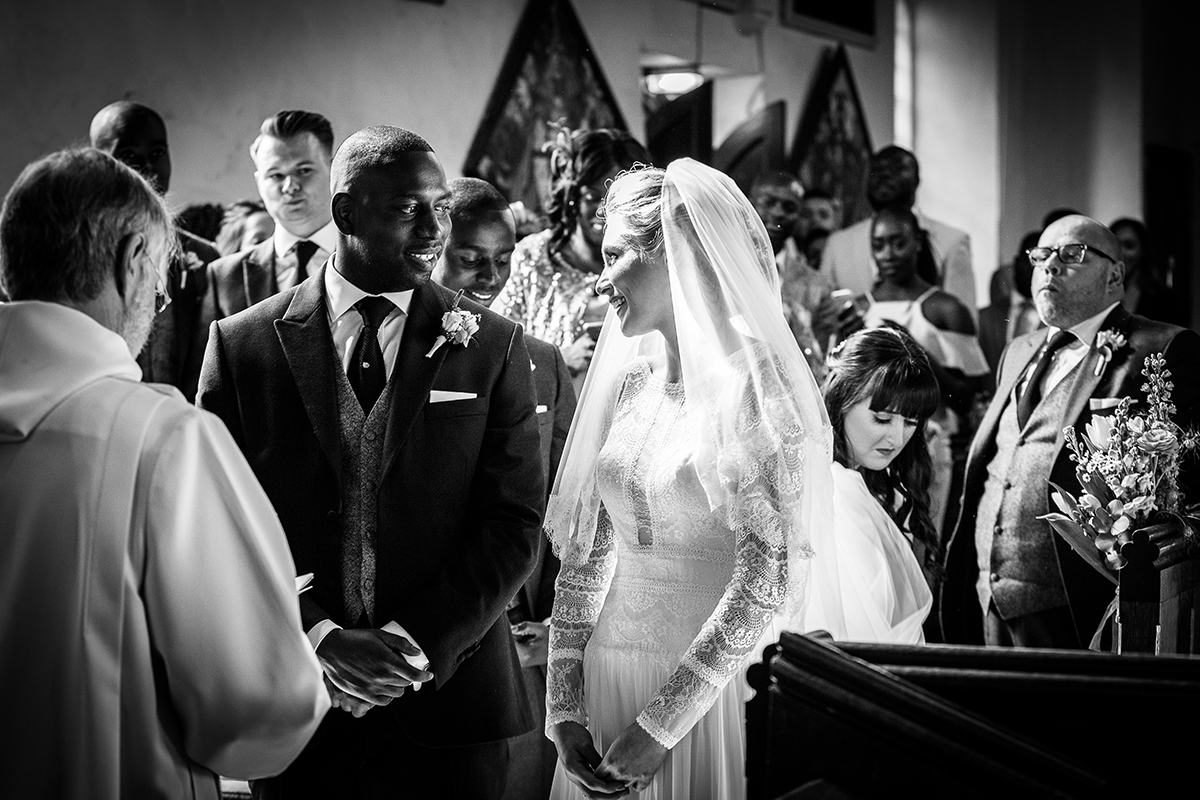 A happy couple say their marriage vows in All Saints Church close to Gaynes Park - wedding reception venues in Essex