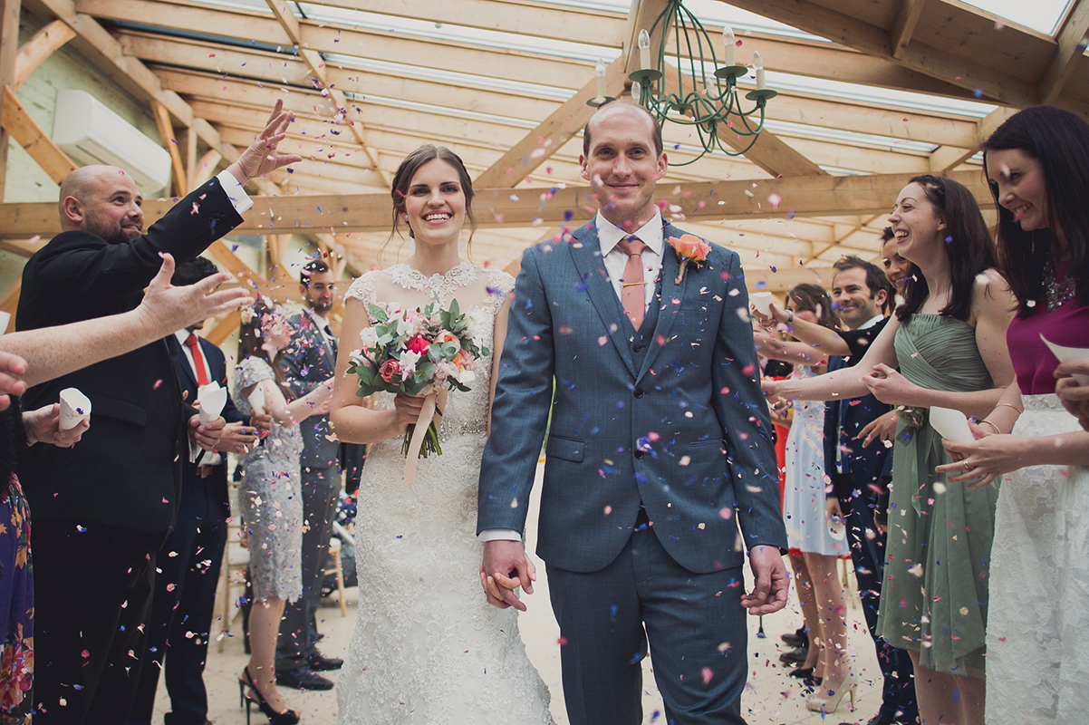 Bride carries a stunning wedding bouquet of summer wedding colours and orange wedding flowers