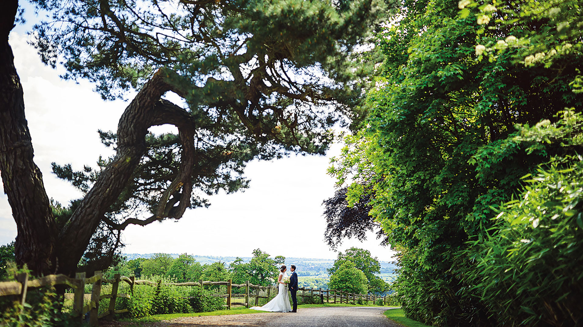 A couple steal a moment away on the entrance drive of this exquisite countryside wedding venue in Essex