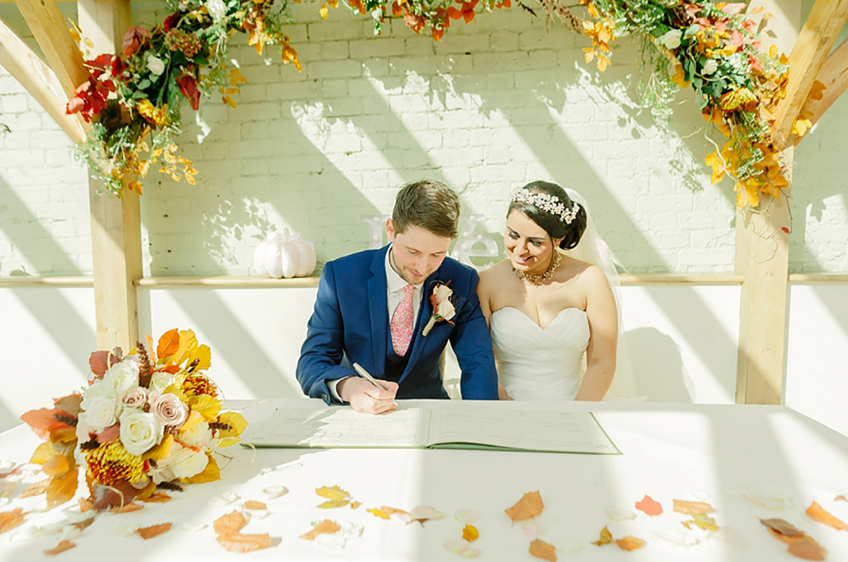 A happy couple sign the register in the stunning wedding ceremony barn - autumn wedding ideas