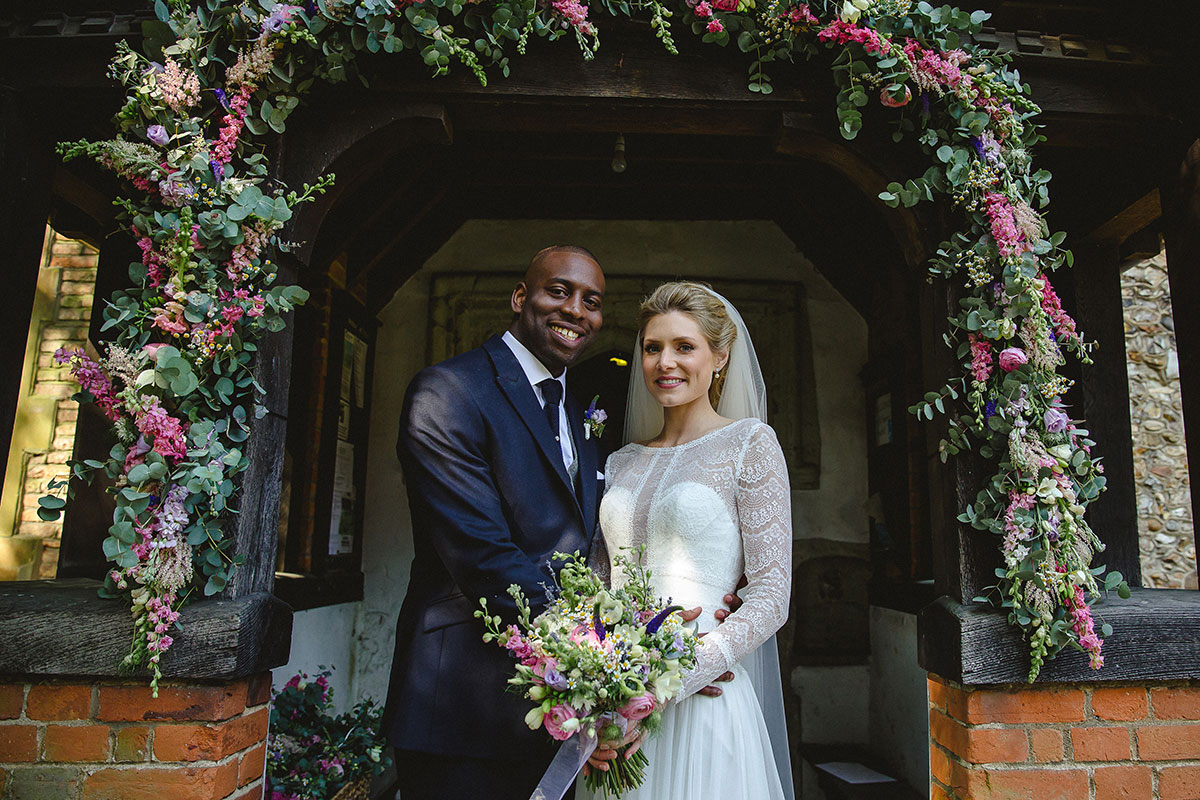 A happy couple smile after saying their marriage vows at All Saints Church - wedding venues in Essex