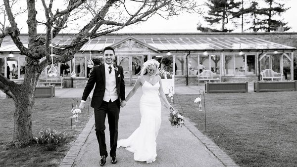 A happy bride and groom walk away from the Orangery after saying their marriage vows in a wedding ceremony
