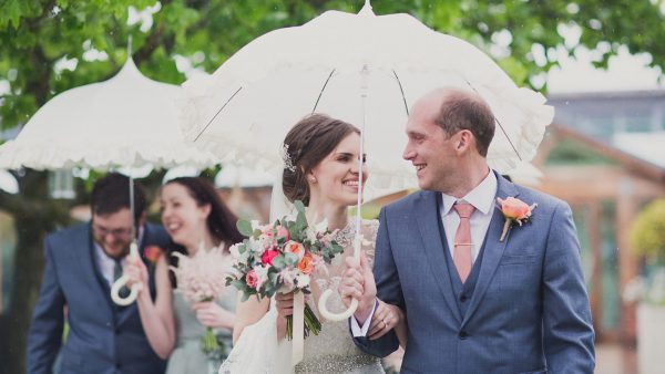 A bride and groom walk together - pink and peach wedding colours are perfect for a summer wedding