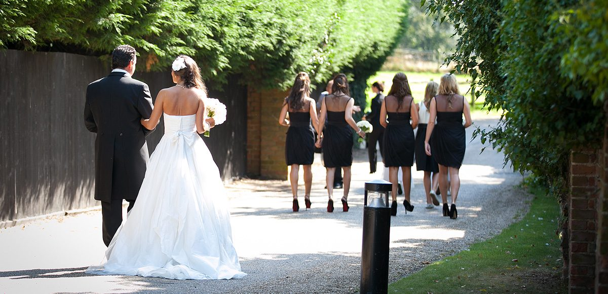 Bride and her father following the bridesmaids to the wedding ceremony at Gaynes Park