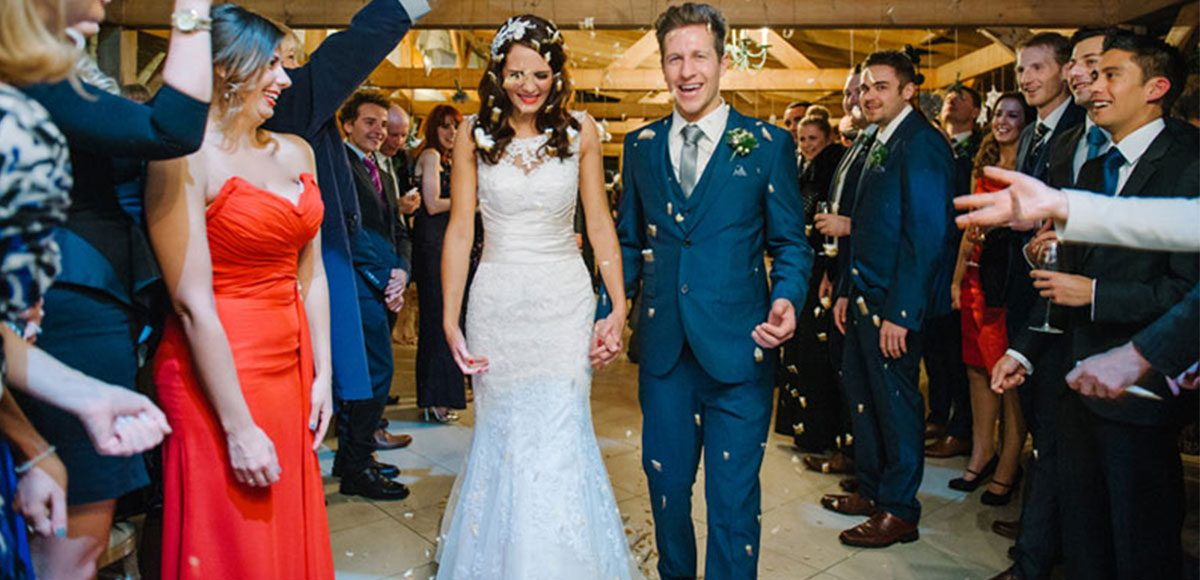 Bride and groom during a confetti throw with wedding guests – barn weddings Essex.