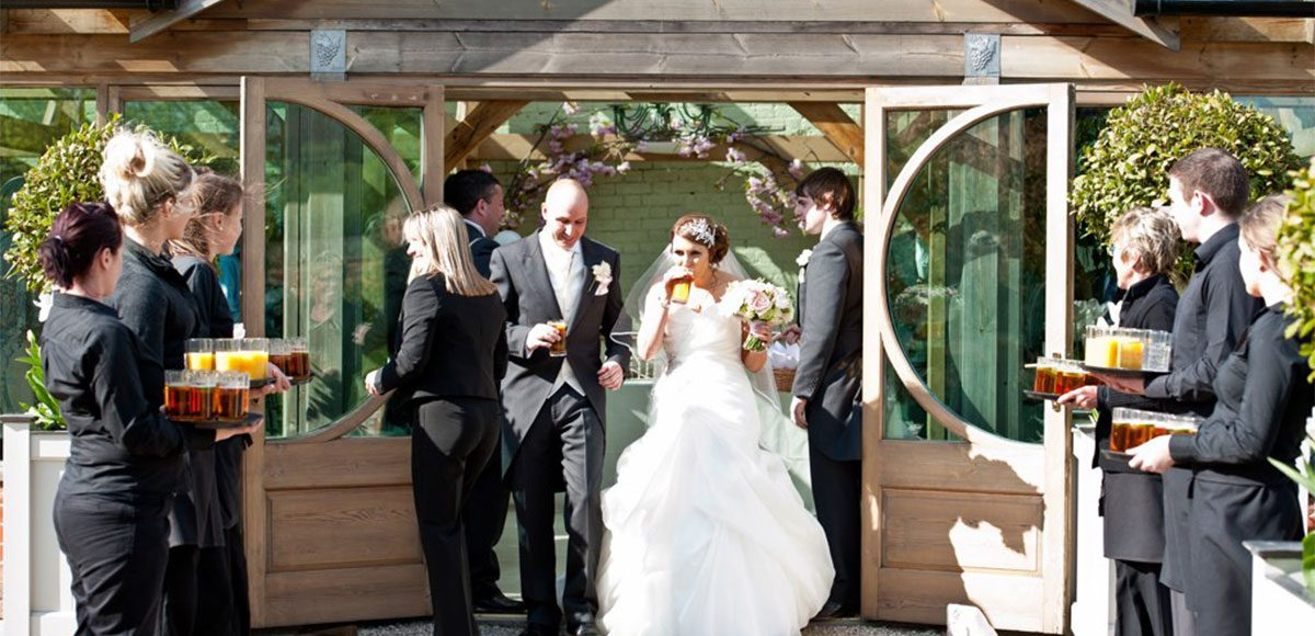 Bride and groom enjoying reception drinks in the Orangery