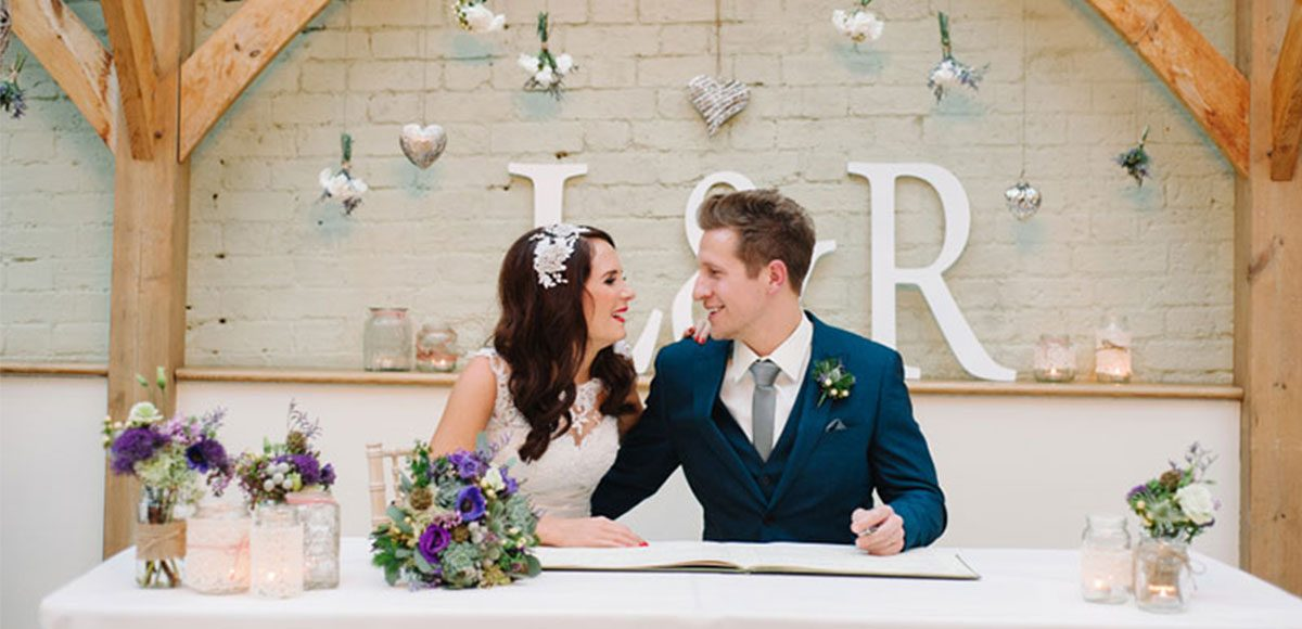 Bride and groom sign the register in the Orangery at Gaynes Park – wedding venue in Essex