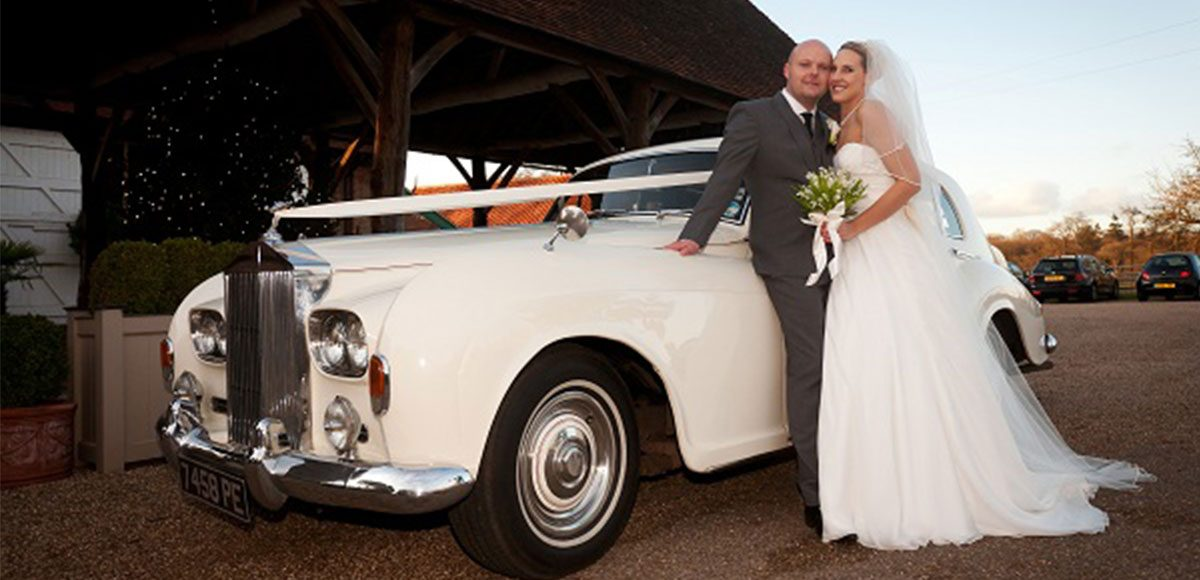 Bride and groom with their vintage wedding transport.