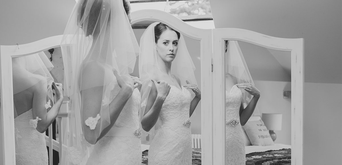 Bride looking in the mirror before her wedding at Gaynes Park