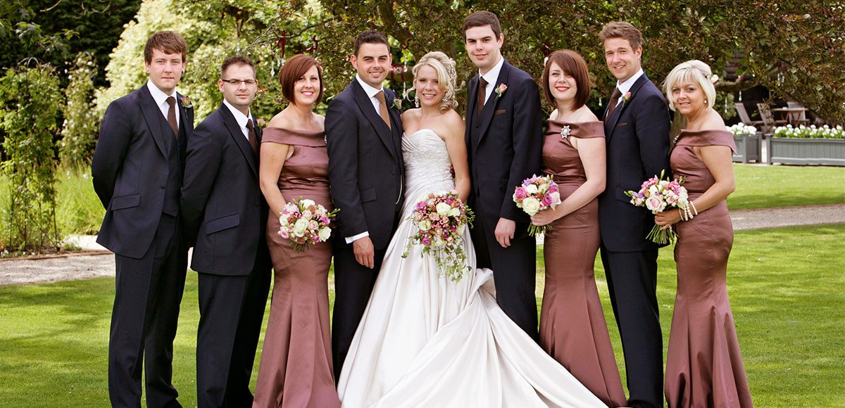 Bride and groom with their bridesmaids and groomsmen in the gardens – Essex wedding venues