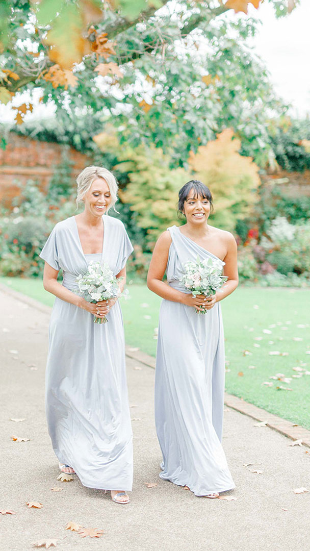 Bridesmaids wear pale blue bridesmaid dresses for their walk down the aisle and to the wedding ceremony barn