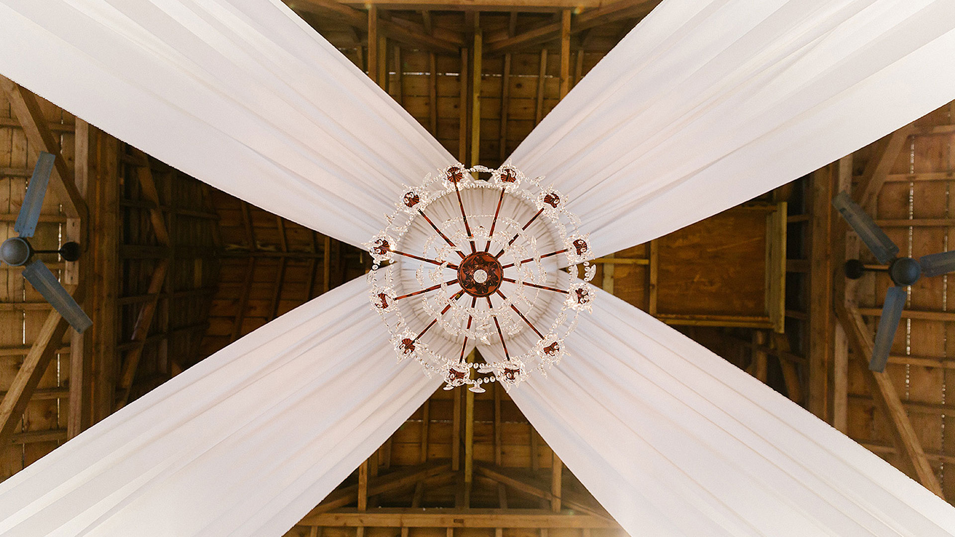 A stunning crystal chandelier hangs from the ceiling in the Mill Barn - wedding decoration ideas
