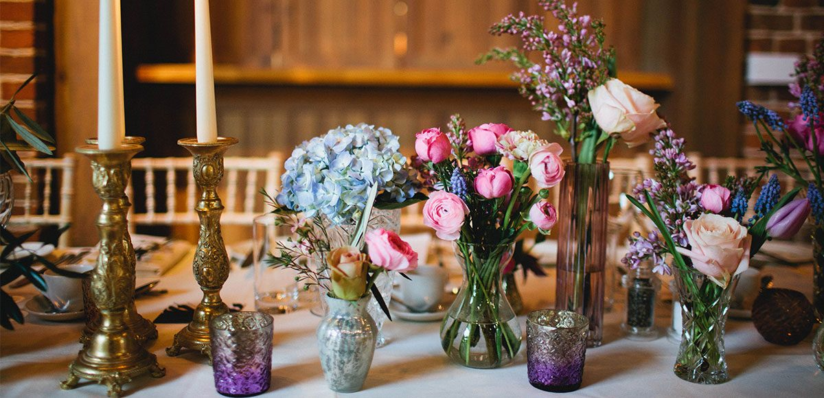 Colourful flowers as table decorations for a barn wedding in Essex