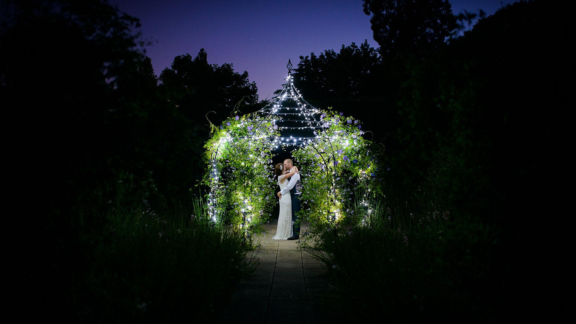 A bride and her bridesmaids make their way to the wedding reception through the romantic Walled Garden