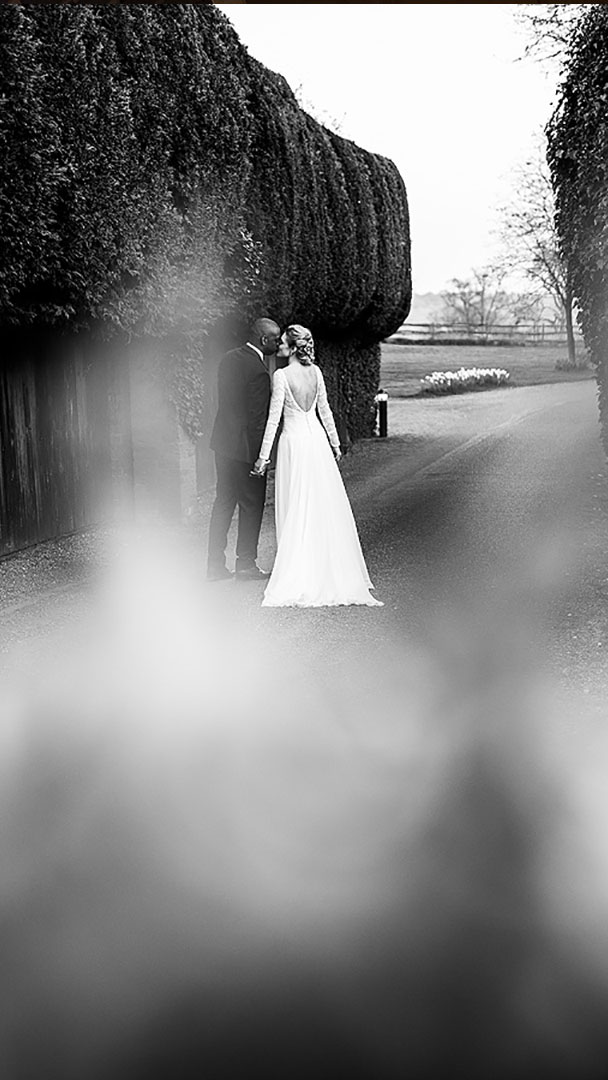A bride and groom kiss as they walk along the wedding entrance drive of the countryside wedding venue