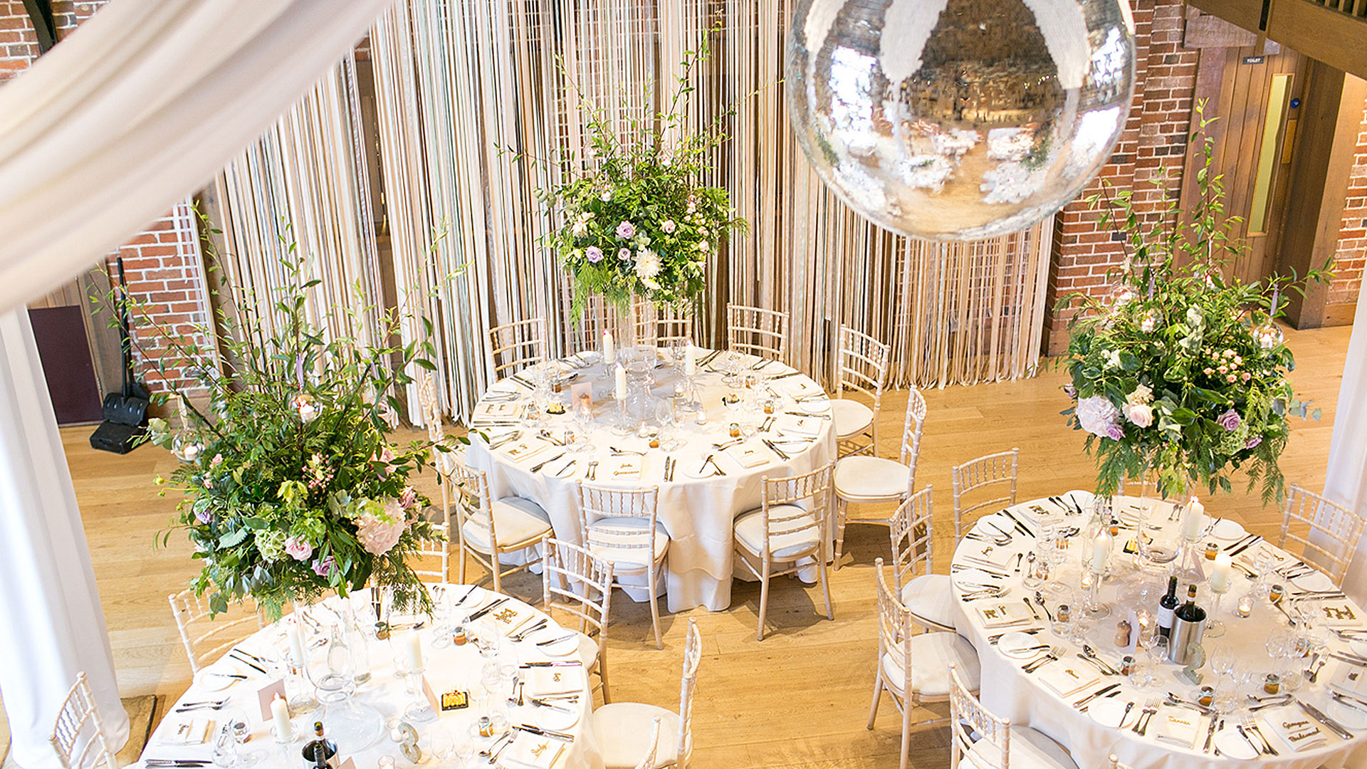 A disco ball hangs from the ceiling in this Essex barn wedding venue - wedding ideas
