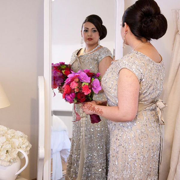 Bride looking in the mirror at her embellished wedding dress