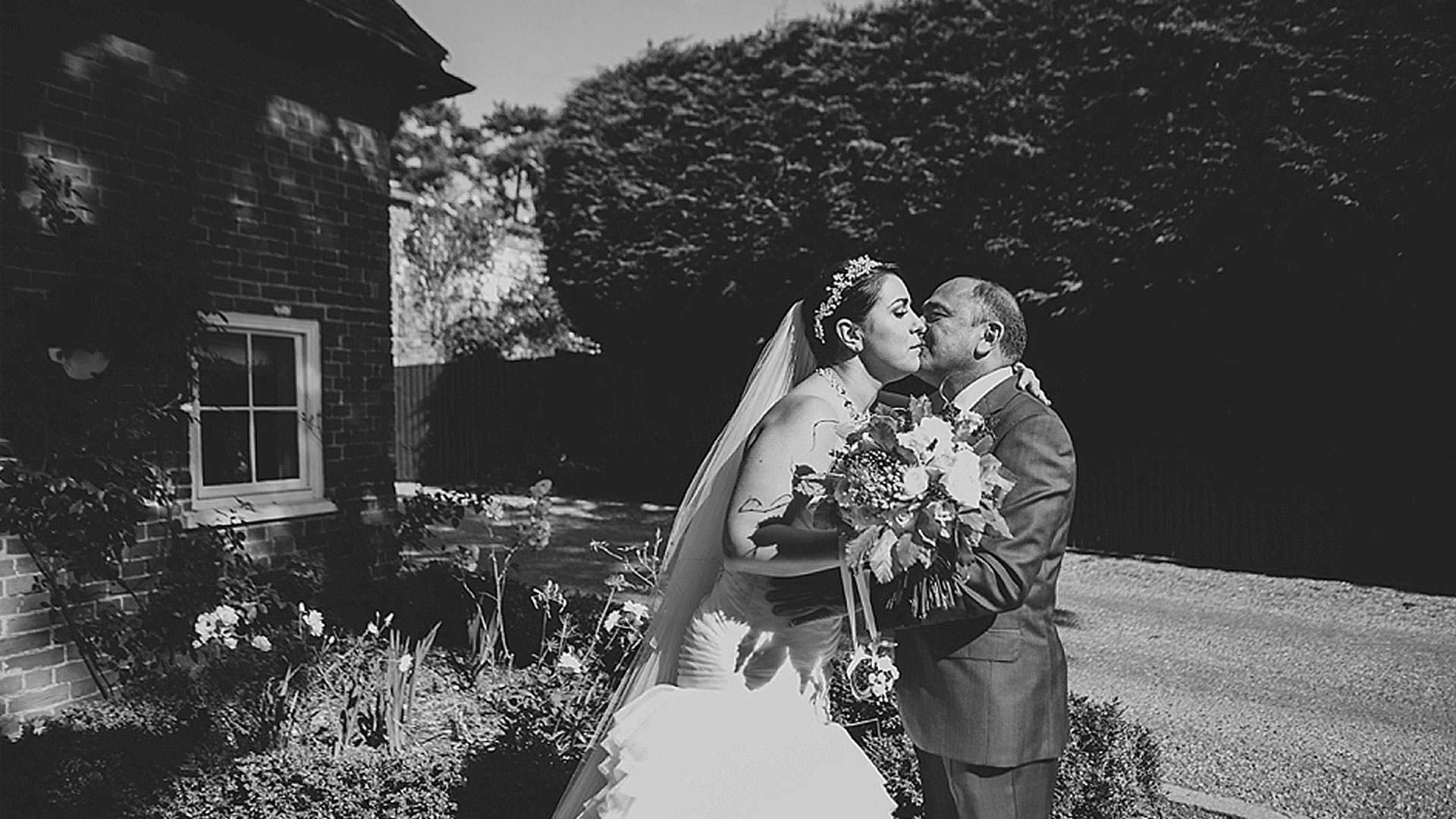 A father kisses the bride outside of the Apple Loft cottage at this Essex wedding venue