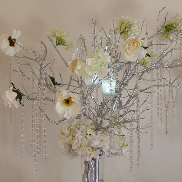 Decorative wood branches painted silver with ivory flowers and crystal decorations
