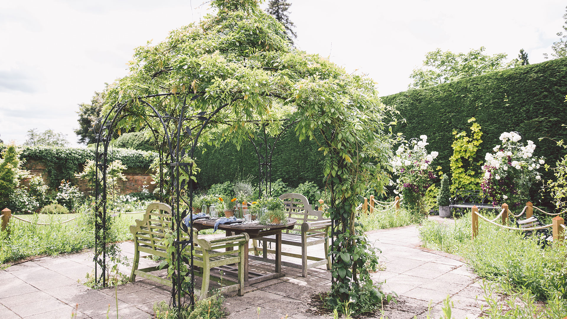 Dine under the wrought-iron pavilion covered in greenery and flora - outdoor weddings in Essex