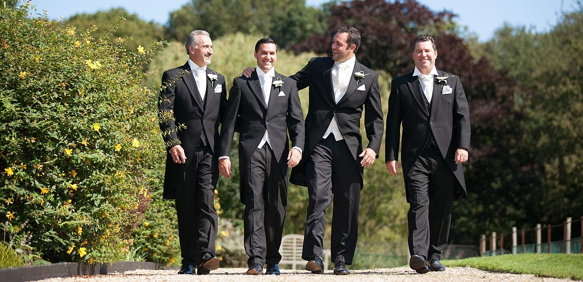 The groom and groomsmen dressed in black tuxedos for a wedding