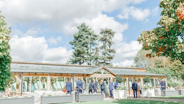 Groomsmen welcome guests to the Orangery ready for the wedding ceremony - barn weddings Essex