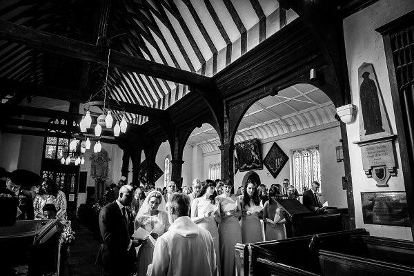 A wedding party sings hymns during their church wedding - wedding barns Essex