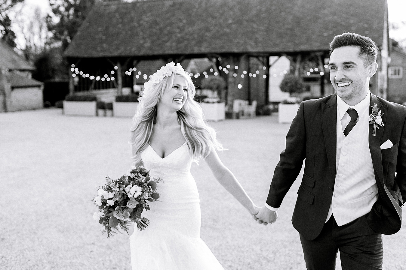 A happy couple are smiling as they walk away from the Gather Barn for wedding photos