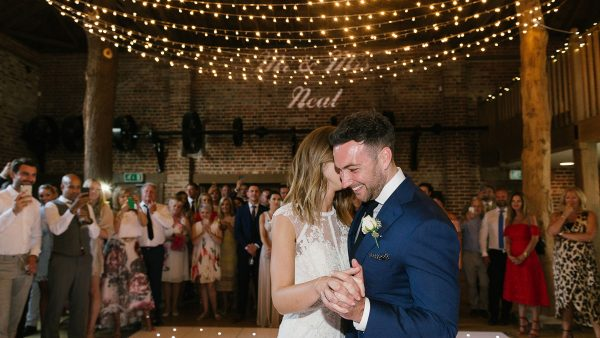 A happy couple enjoy their first wedding dance inside the Mill Barn with exposed tree trunks - wedding barns Essex