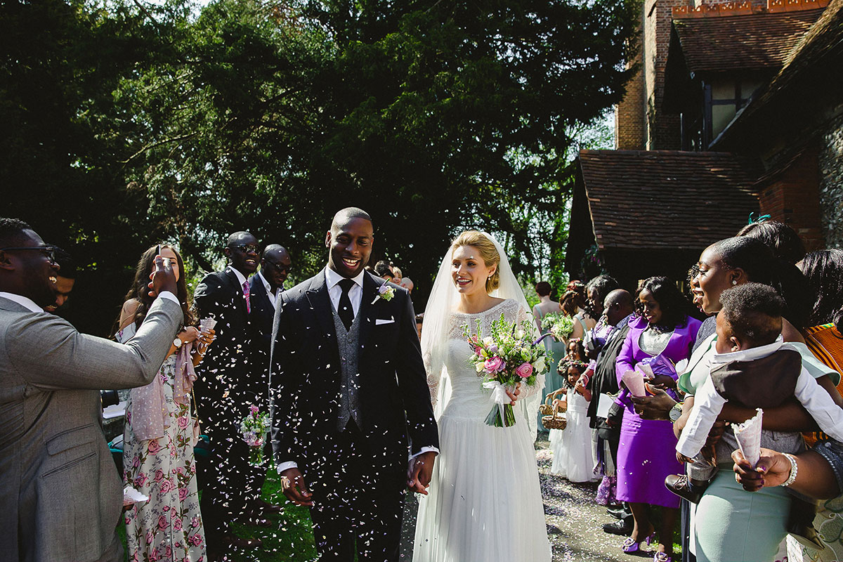 Guests throw confetti at a happy couple after their church wedding in Essex
