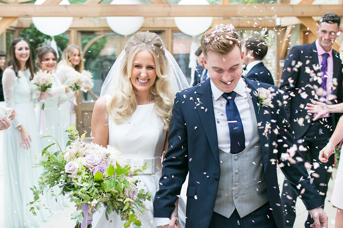 A bride and groom leave the wedding ceremony barn as guests throw confetti - Essex wedding venue