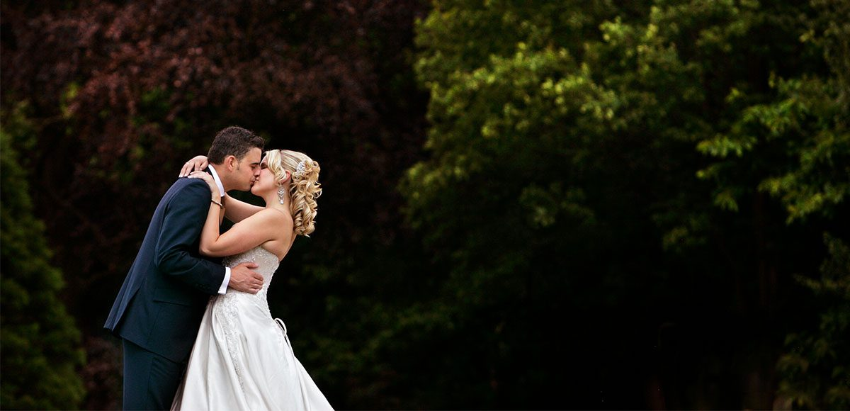 Bride and groom kissing in the gardens at Gaynes Park