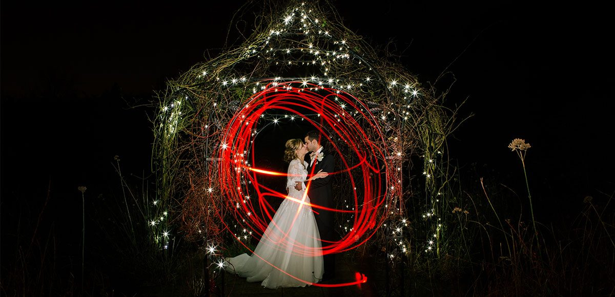 Couple pose for a light trail photo in the gardens at night.
