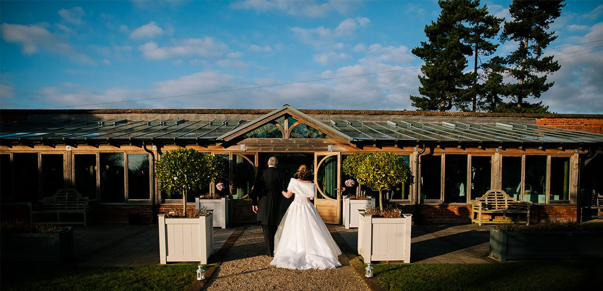 Bride walking down the Long Walk to the aisle inside of the Orangery – venue hire Essex.
