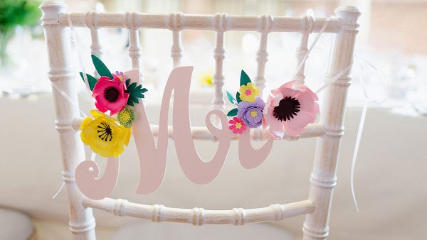 A white wooden chair decorated with colourful paper flowers and Mr wedding sign - wedding decoration ideas