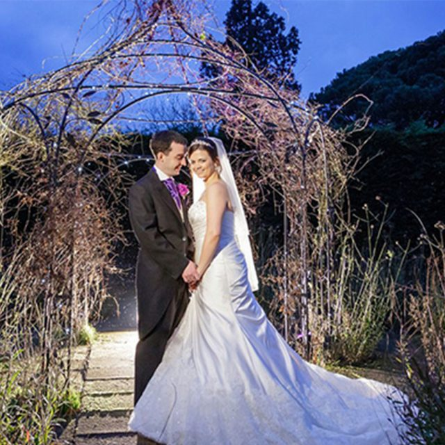 Bride and groom in the gardens of Gaynes Park at night.