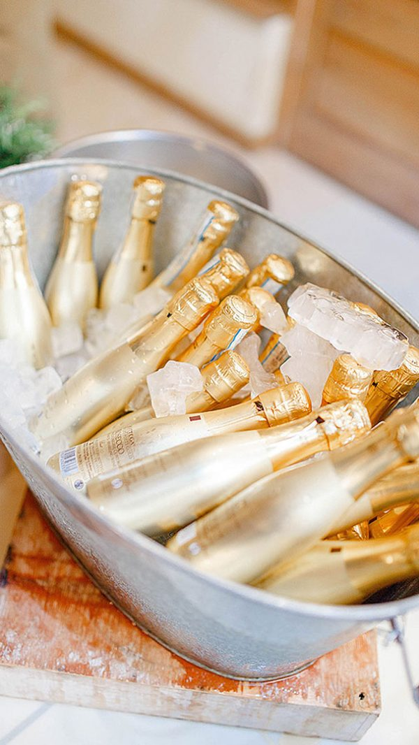 Treat guests to small champagne bottles presented in a rustic metal container - wedding drink ideas