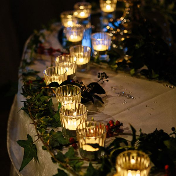 Table decorated with candles and holly for a winter wedding.