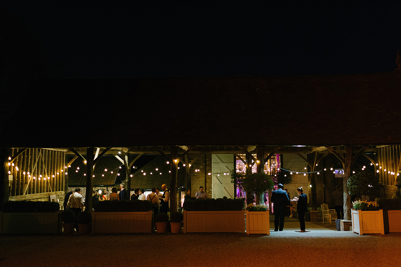 The open-sided Gather Barn is perfect for guests to catch some fresh air during the evening wedding reception