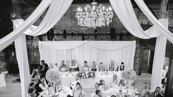White drapes and a chandelier adorn the ceiling of this stunning barn wedding venue in Essex